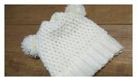 ポンポンつけた白のニット帽